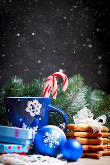 Filiżanki kakao, ciastka, prezenty i jedlinowe gałąź na drewnianym stole.