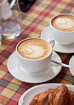 Filiżanki kawy cappuccino z rogalikiem w kawiarni
