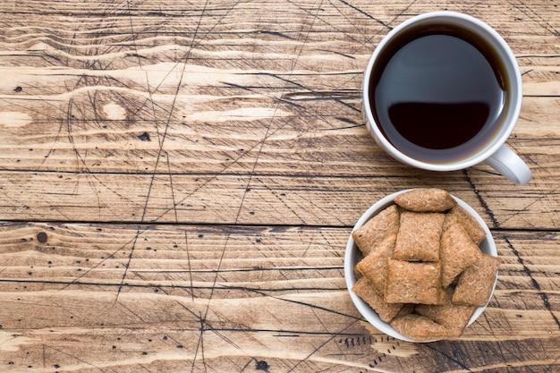 Filiżanki kawy i ciastek krakers na drewnianym stole.
