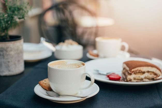 Filiżanki kawy i tiramisu na czarnym stole z pięknym sercem w kształcie latte art.