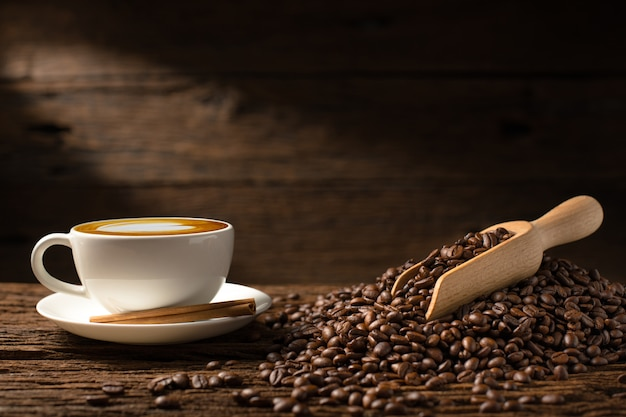 Filiżanki kawy latte i kawowe fasole na starym drewnianym tle