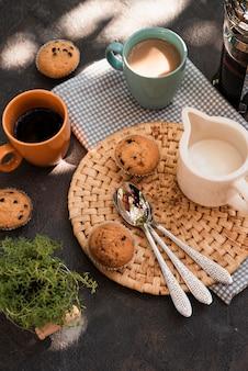 Filiżanki kawy pod dużym kątem z babeczkami