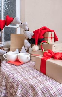 Filiżanki kawy, serduszka, torba na zakupy i prezenty na świątecznym stole w domu.