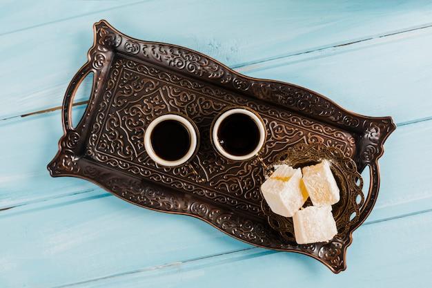 Filiżanki kawy w pobliżu spodek ze słodkimi tureckimi przysmakami na tacy