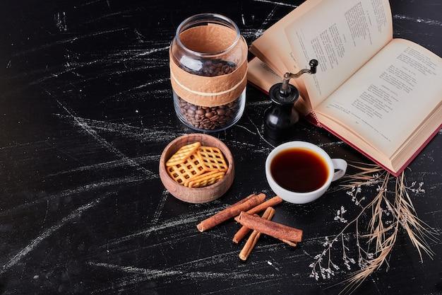 Filiżanki kawy z ciastkiem i cynamonami.