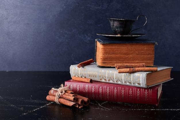Filiżanki kawy z cynamonami na książkach.