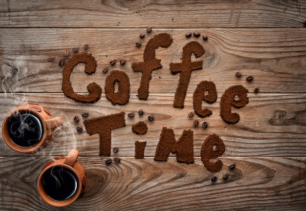 Filiżanki kawy z kontrparą na textured drewnianym tle.