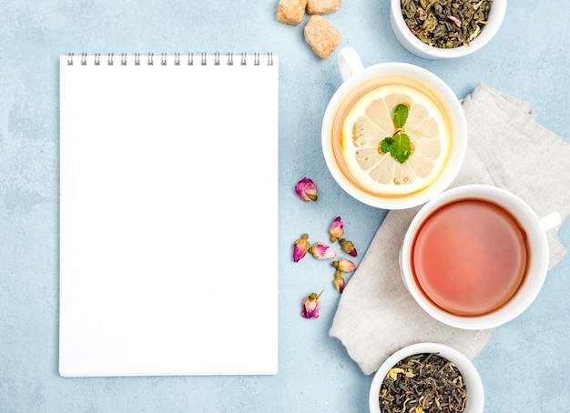 Filiżanki leżące na płasko z herbatą i notatnikiem
