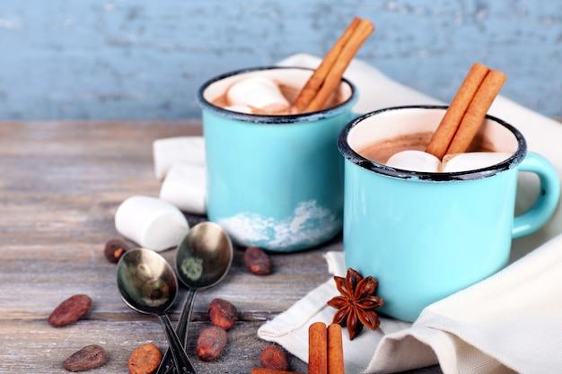 Filiżanki smacznego gorącego kakao, na drewnianym stole,