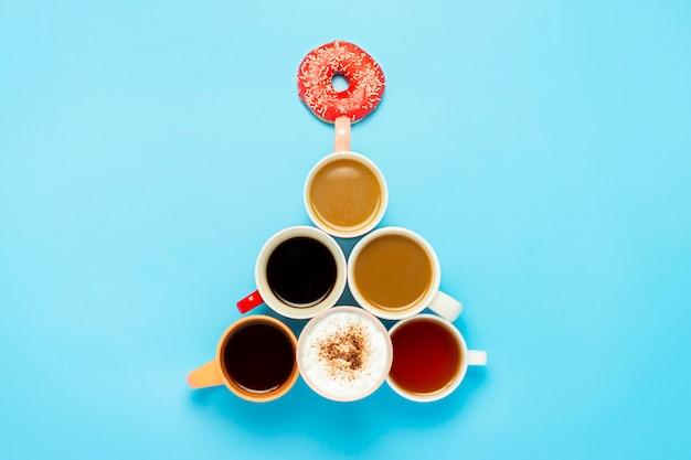Filiżanki z gorącymi napojami, kawa, cappuccino, kawa z mlekiem, kształt choinki, niebieska powierzchnia.