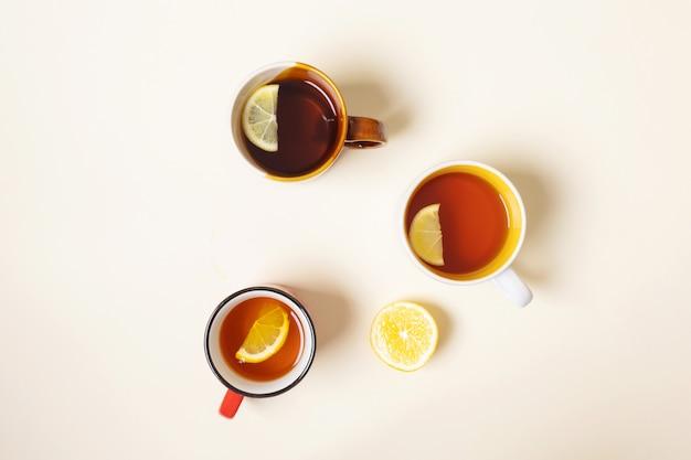 Filiżanki z herbatą z cytryną na beżowym tle.