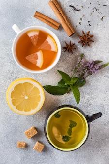Filiżanki z inną herbatą czerwony, zielony i czarny na szarym stole.