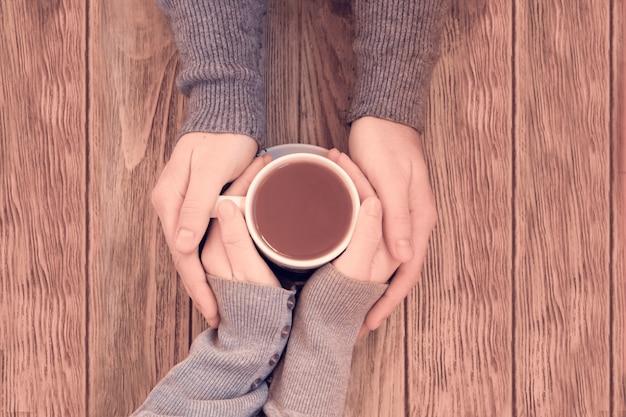 Filiżanki z kawą w rękach kobiet i mężczyzn.