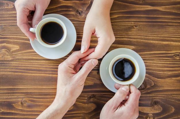 Filiżanki z kawą w rękach mężczyzn i kobiet.