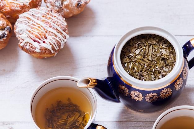 Filiżanki z parzoną herbatą, czajnikiem i babeczkami na białym drewnianym stole