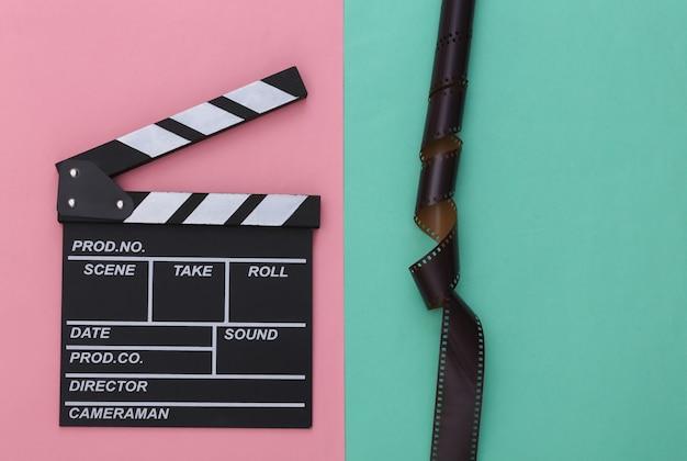 Film clapper board z taśmą filmową na różowym niebieskim tle pastelowych. produkcja filmowa, produkcja filmowa, przemysł rozrywkowy. widok z góry