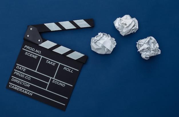 Film clapper board z zmiętymi papierowymi kulkami na klasycznym niebieskim tle. produkcja filmowa, produkcja filmowa. kolor 2020. widok z góry