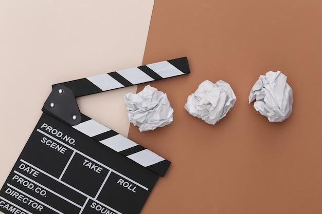 Film clapper deska z zmiętymi papierowymi kulkami na beżowym brązowym tle. produkcja filmowa, produkcja filmowa. widok z góry
