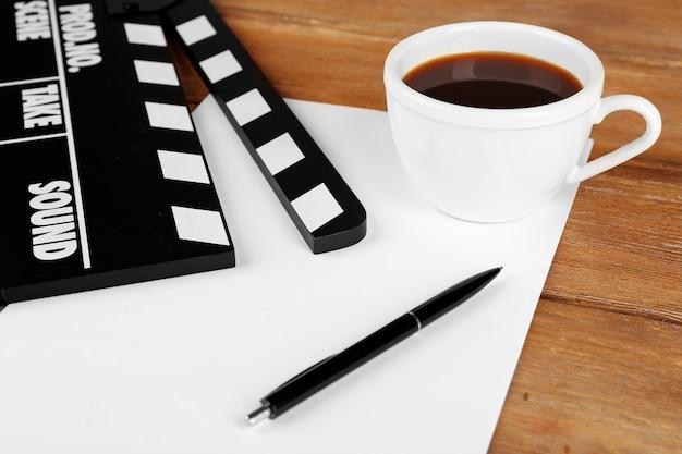 Film grzechotka z papierem, długopisem i filiżanką kawy na drewnianych deskach