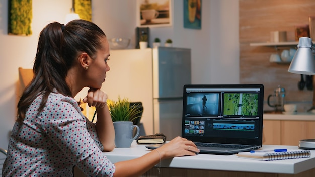 Filmowiec edycji z domu na profesjonalnym laptopie siedząc na biurku w nowoczesnej kuchni o północy. kreatywny montażysta wideo pracujący w nocy przy nowym projekcie, przetwarzający montaż dźwięku filmowego.