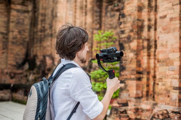 Filmowiec-mężczyzna kręci wideo w elektronicznym stabilizatorze, steadycam aby kręcić w po nagar cham tovers. koncepcja technologii cyfrowej. .