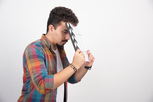 Filmowiec trzymający pustą tablicę klapy, wygląda na zmęczonego i znudzonego.