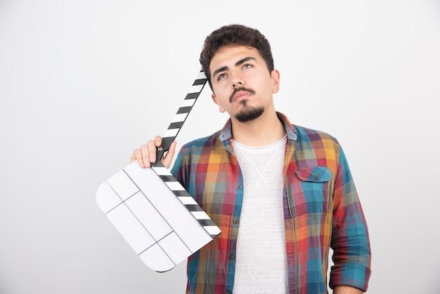 Filmowiec z deską klapy wygląda zamyślony.