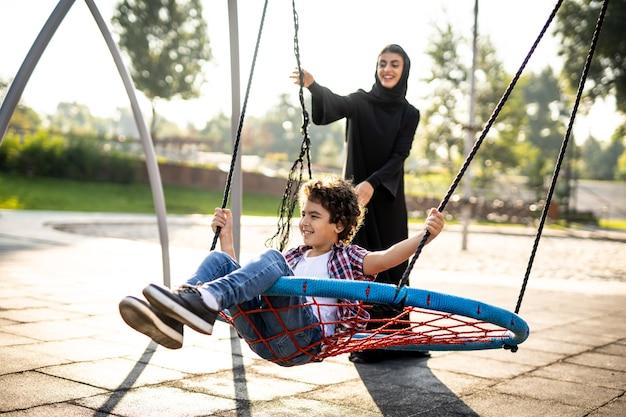 Filmowy obraz kobiety z emiratów z dziećmi bawiącymi się na placu zabaw