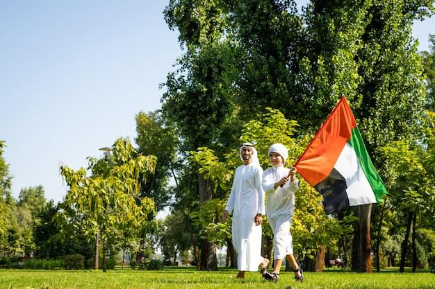 Filmowy obraz rodziny z emiratów spędzającej czas w parku. młody mężczyzna grający w piłkę nożną na trawie