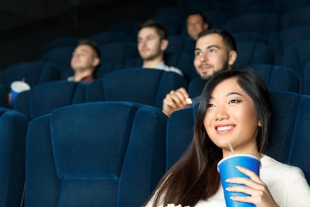 Filmy dzisiaj. zamyka w górę niskiego kąta strzału piękna azjatycka kobieta ono uśmiecha się podczas oglądania filmów
