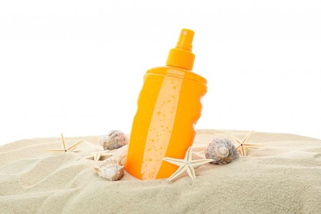 Filtr przeciwsłoneczny z rozgwiazdą i seashells na jasnym dennym piasku odizolowywającym na białym tle. letni wypoczynek
