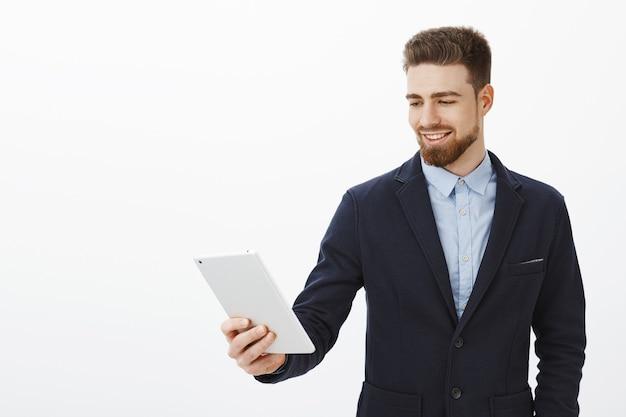 Finanse, gig economy i koncepcja biznesowa. pewny siebie, zadowolony, odnoszący sukcesy przedsiębiorca męski w eleganckim, stylowym garniturze, trzymający cyfrowy tablet wpatrzony w ekran gadżetu, zadowolony z pewnego uśmiechu