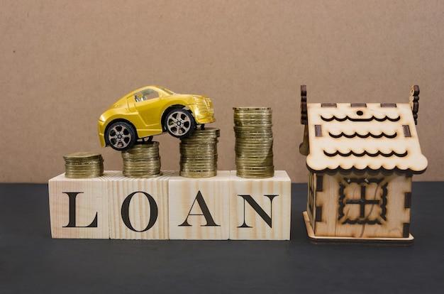 Finanse i kredyty samochodowe kredyty samochodowe żółte auto i drewniany dom drewniane kostki z napisem pożyczka miejsce na tekst spłata kredytu samochodowego i domu