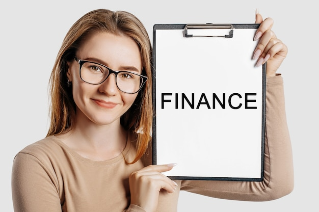 Finanse. piękna młoda biznesowa kobieta w okularach trzyma schowek z makietą miejsca na szarym tle