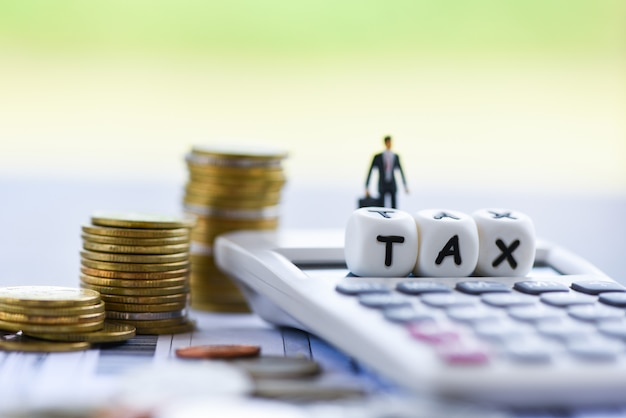 Finanse podatkowe biznesmen kalkulator ułożone monety na rachunku faktury papieru na czas wypełniania podatku zapłaconej spłaty zadłużenia
