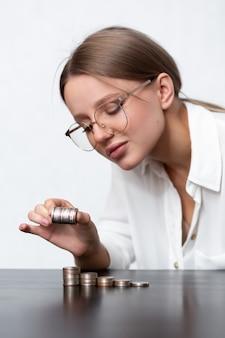 Finansistka bierze stos monet i układa je w inne stosy na stole. liczy pieniądze w ręku. pojęcie oszczędzania pieniędzy, polityki finansowej i inwestycyjnej.