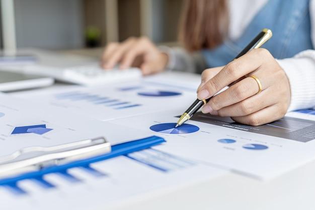 Finansistka wskazuje długopisem dokument, analizuje i sprawdza poprawność danych finansowych firmy przed przedstawieniem ich na spotkaniu. koncepcja audytu finansowego.