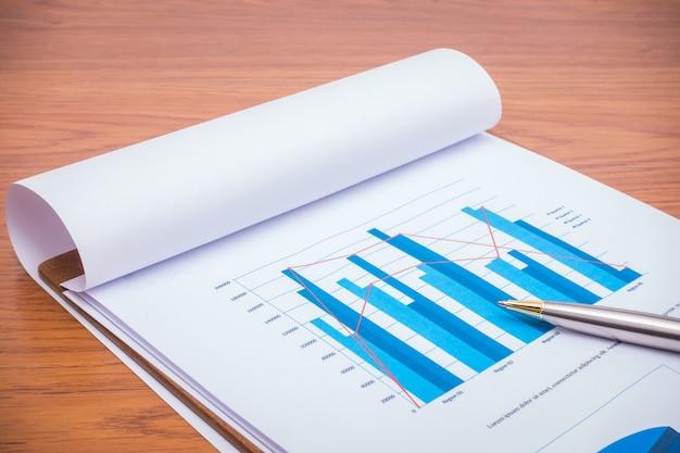 Finansowego wykresy z piórem na stole