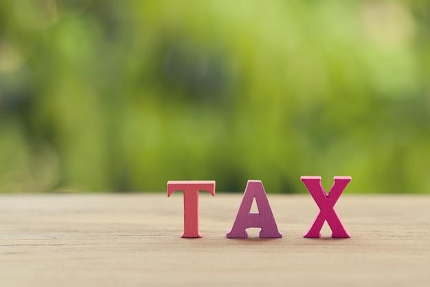 Finansowy podatku pojęcie: przygotowań listów drewniany słowo podatek na stole. przedstawia podatek ad valorem od wartości nieruchomości w sposób zgodny z prawem