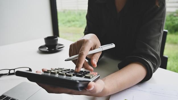 Finansowy pojęcie, kobiety obliczenia finanse dane na stole.