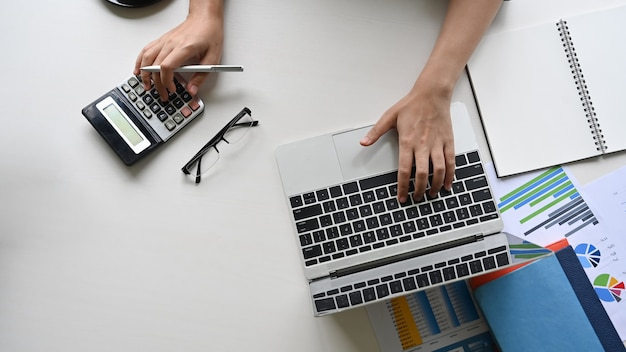 Finansowy pojęcie, odgórnego widoku żeńskiej ręki pisać na maszynie kalkulator i laptop na biurowym biurku.
