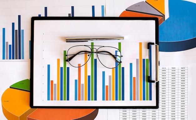 Finansowy wykres i wykres z piórem i okularami