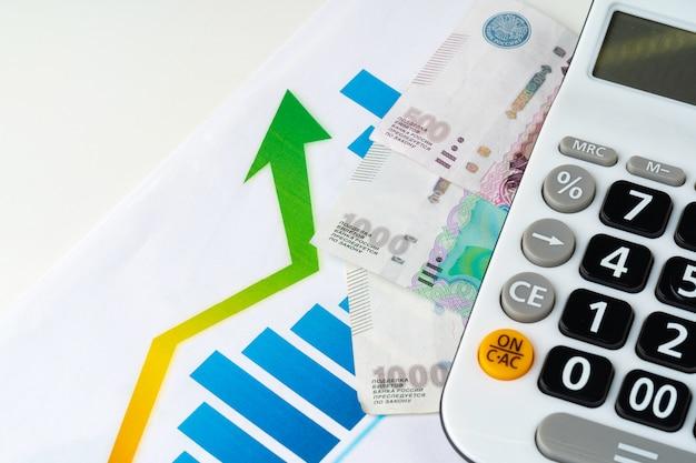 Finansowy wykres z rosyjskich rubli stos pieniędzy z kalkulatora. koncepcja wzrostu wartości waluty