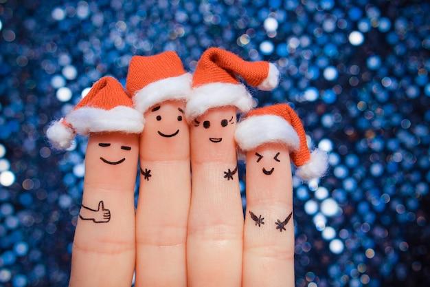 Finger art przyjaciół świętuje boże narodzenie. pojęcie grupy ludzi śmiejących się w noworocznych czapkach. stonowany obraz.