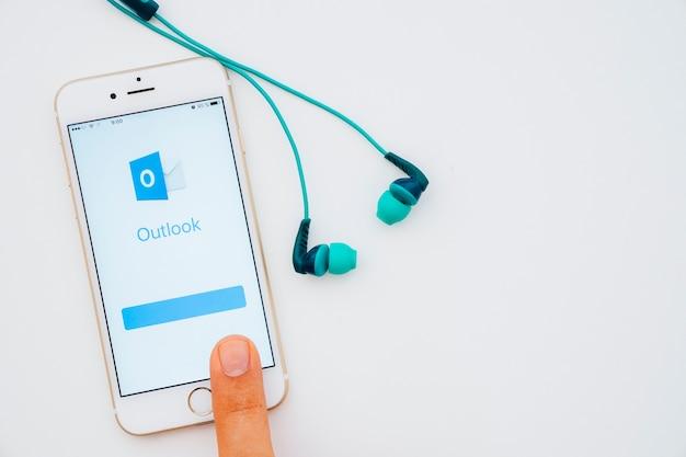 Finger dotyka ekranu z aplikacji outlook i słuchawek