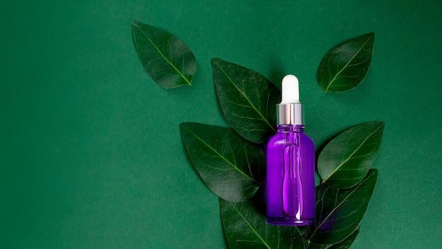 Fioletowa butelka kosmetyków na zielonym tle, leży na świeżych liściach. makieta kosmetyczna, koncepcja ekologiczna. duży baner z miejscem na kopię.