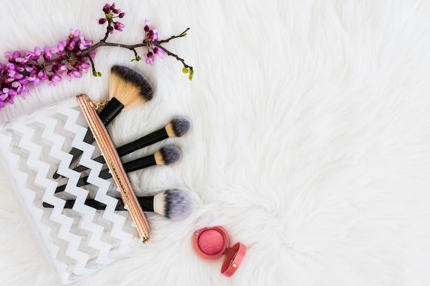 Fioletowa gałązka z pędzlami do makijażu i różowym pudrem do twarzy na białym futrze