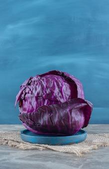 Fioletowa kapusta na drewnianym talerzu, na podstawce, na marmurowym stole.