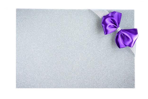 Fioletowa kokardka ze srebrną wstążką na tle fioletowego brokatu. świąteczne tło.