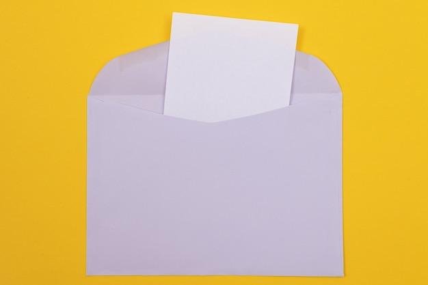 Fioletowa koperta z pustą białą kartką papieru w środku